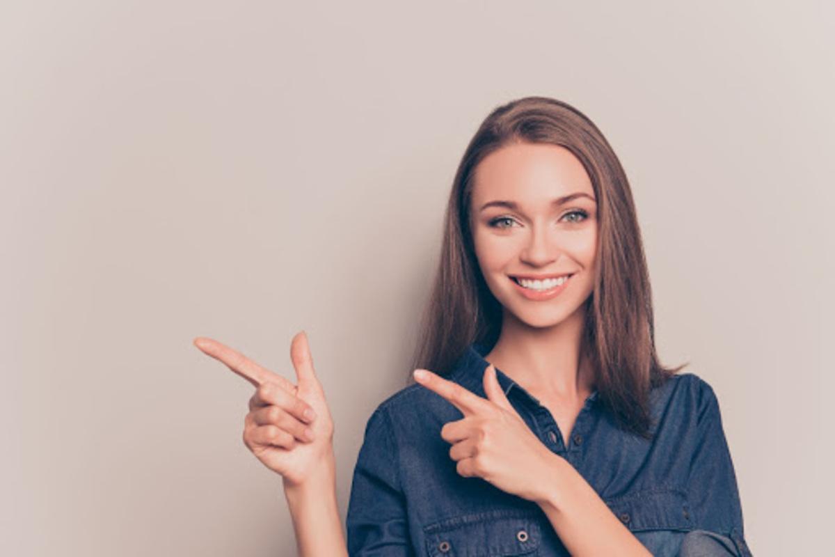 女性 指さし 笑顔